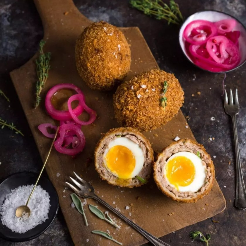 A platter of homemade Scotch Eggs, sliced to reveal the runny yolk