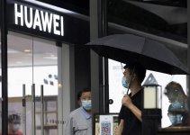 Seorang Pria Berdiri di depan Gerai Huawei di Beijing, dampak persaingan dagang di bawah tekanan Amerika Serikat