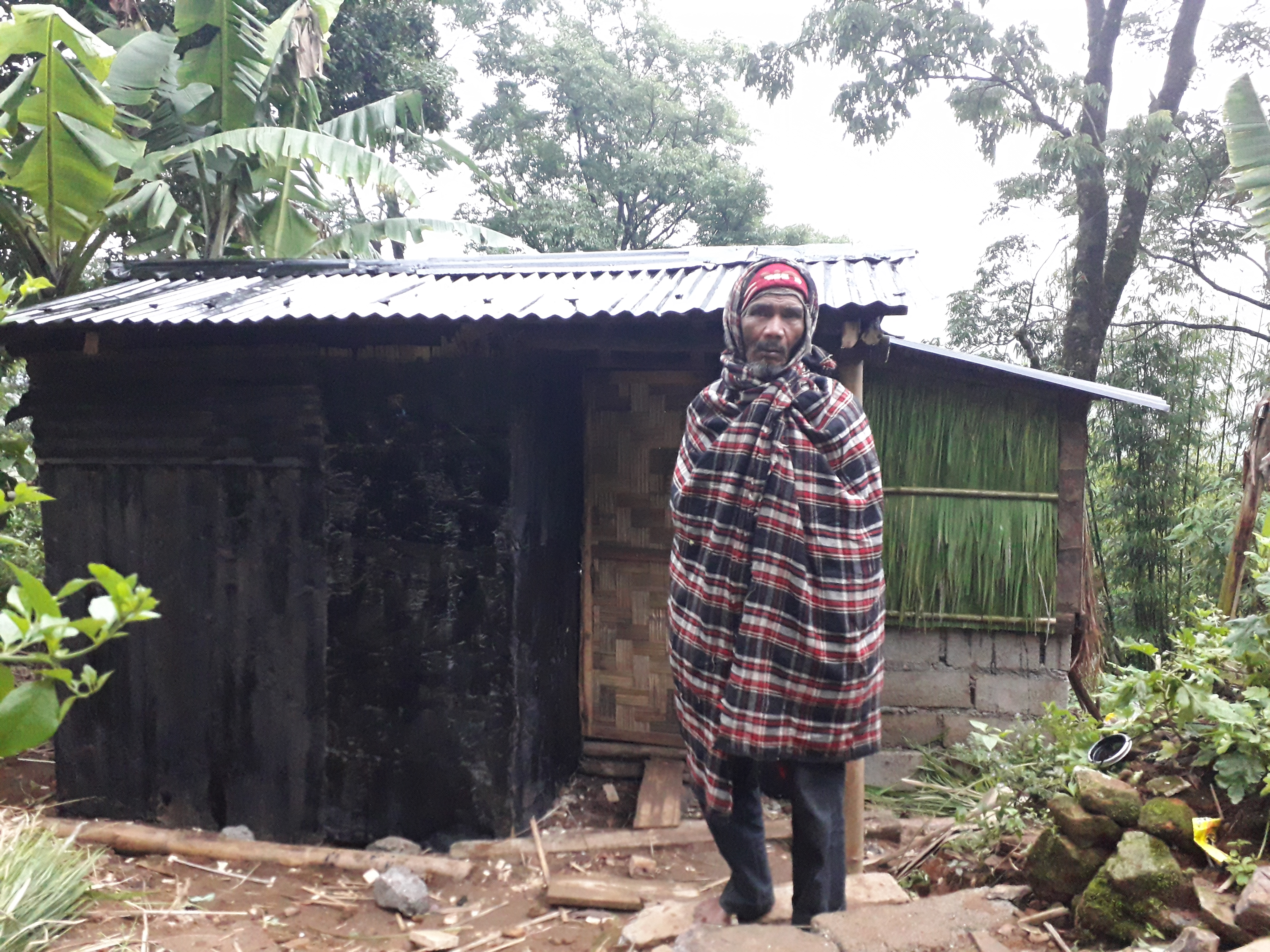 Bah Barno Dohling in front of his new house