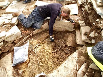 Claire investigates the deposits under the large flagstone.