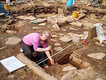 Sarah records the hearth in Structure 10.