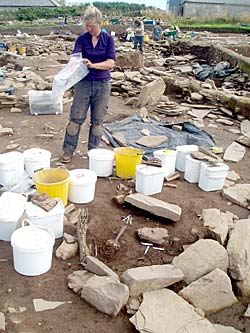 Georgie surrounded by a sea of sample buckets tackling her Neolithic loo.