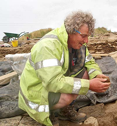 Prof Mark Edmonds can't hide his delight at the discovery of the carved stone ball.