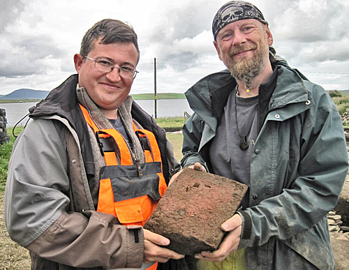 Hugo and Mike display the bright-red, dressed-sandstone block from the robber trench on the south side of Structure Ten.
