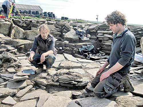 Owain and Dan unravel the complexities of the paving and wall lines around the central standing stone.