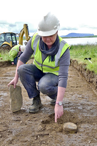 Anne points to the pot base revealed in the new trench.