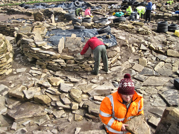 Giles removes a decorated stone from the vestiges of Structure Eleven.
