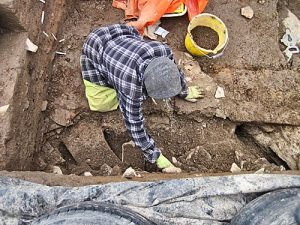 Mai uncovering the remains of the wall of the putative chambered cairn in Trench T.