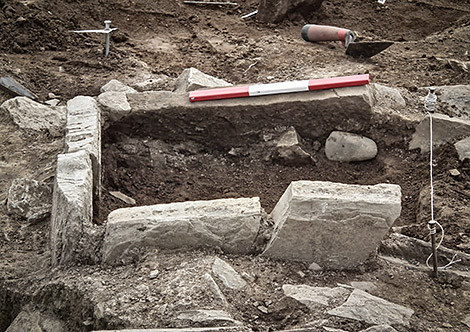 The camptonite axe found in the Trench J extension hearth in situ.