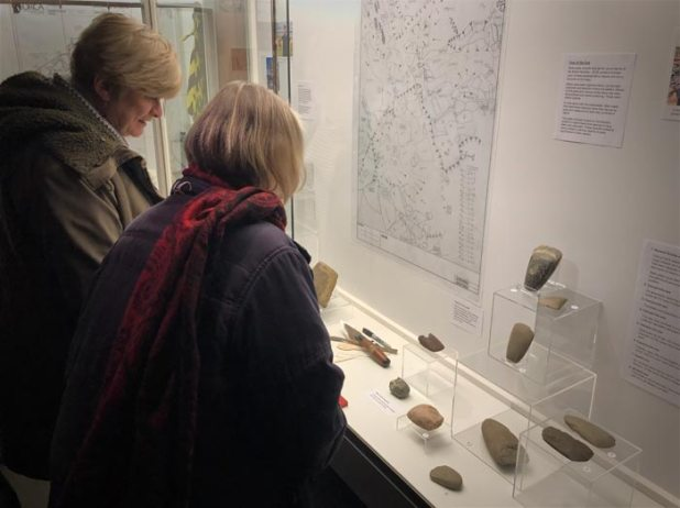 Guests view the maceheads and axes from the 2018 excavation.