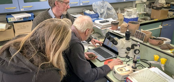 Site director Nick Card with pottery specialists Roy Towers and Jan Blatchford examine the latest mat impress base in the lab.