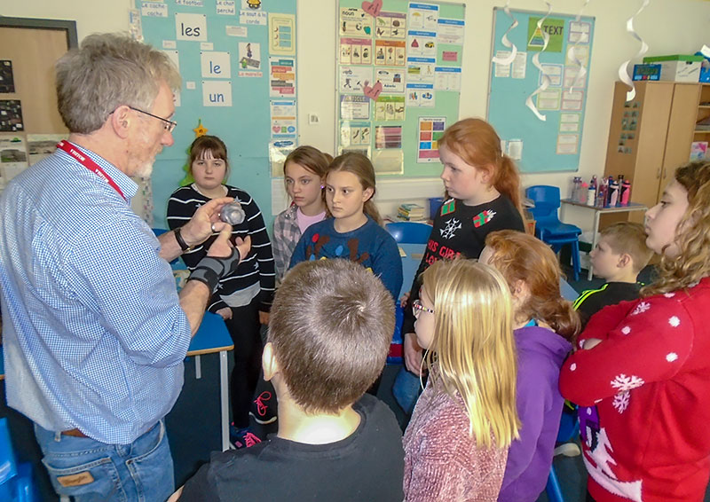 Nick Card shows pupils from Evie Community School a replica of the carved stone ball found at the Ness of Brodgar excavation site.