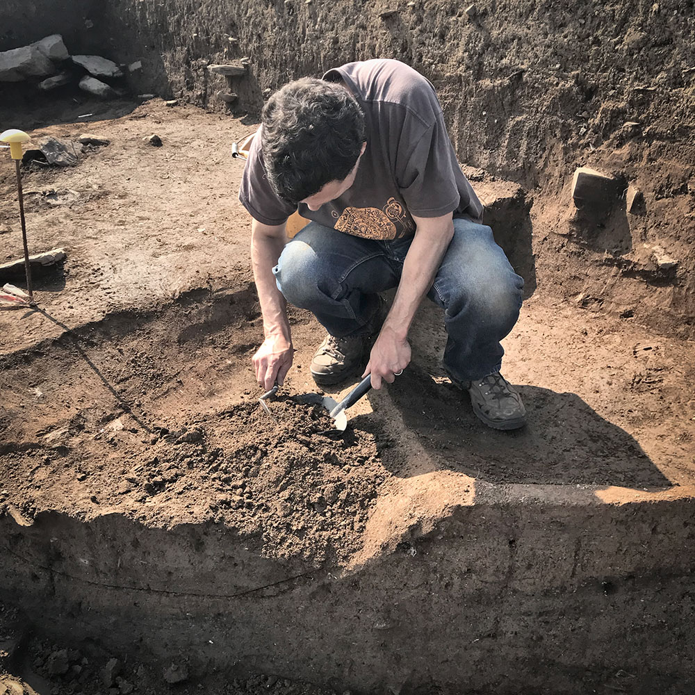 Robert excavating a pit in the western extension of Trench T.