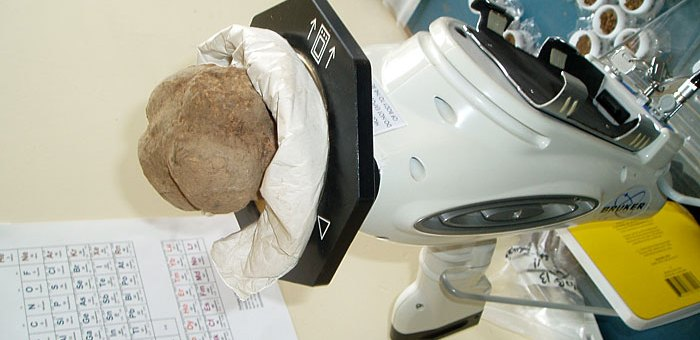 2013: Fresh from Structure Ten, the carved stone ball is subjected to chemical analysis using Professor Scott Pike's portable XRF equipment. (ORCA)