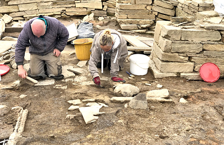 Kevin and Jenna at work on the floor inside Structure Twelve, which has revealed an interesting stone feature - probably relating to interior 'furniture' - pictured directly in front of Jenna. (Sigurd Towrie)