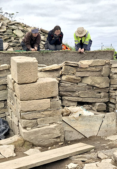 Jenna, Andy and Clare discuss the differing layers encountered in the trench extension outside the blocked north-western entrance to Structure Twelve. (Sigurd Towrie)