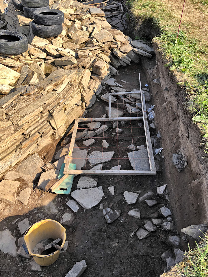Clare's planning frames over the paving and structural features outside Structure Twelve's south-western corner. If there's anything you want to know about planning, ask Clare! (Sigurd Towrie)