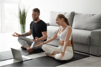 Man and woman looking at computer while holding a yoga pose