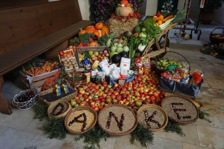 Erntedank-Gaben. Viele Äpfel und Gemüsesorten, Mehl und auch Brot und Milch