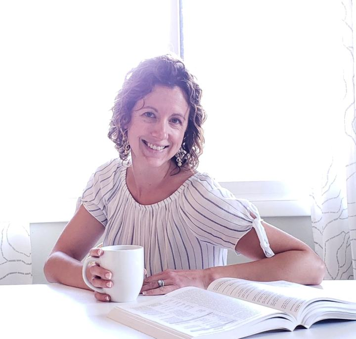 picture of Laura Duffy sitting at a table with a mug and book