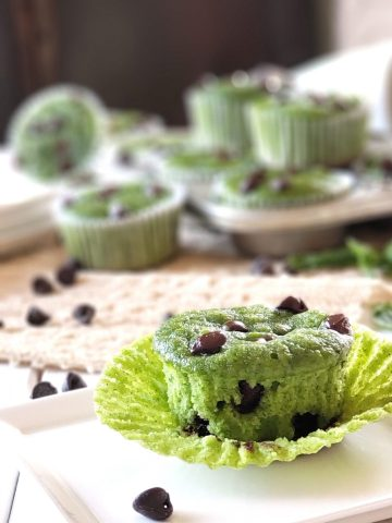 closeup photo of a green chocolate chip muffin unwrapped with more green chocolate chip muffins in the background