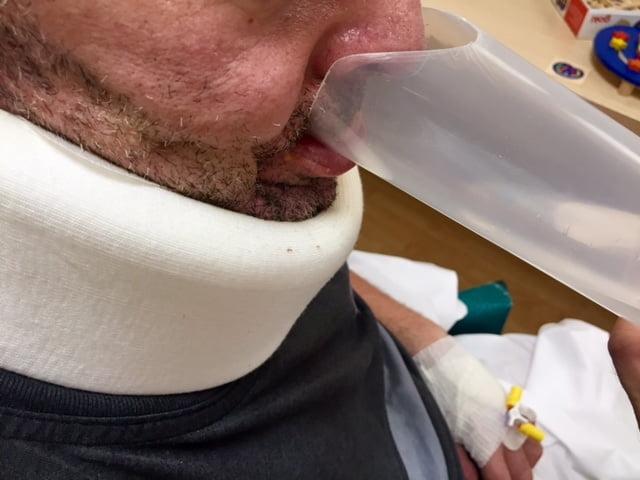 Paciente con disfagia bebiendo en el vaso de plástico adaptado