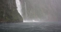 Wasserfall und Boot auf dem Wasser des Milford Sounds