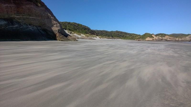 Wind treibt den Sand über den Strand