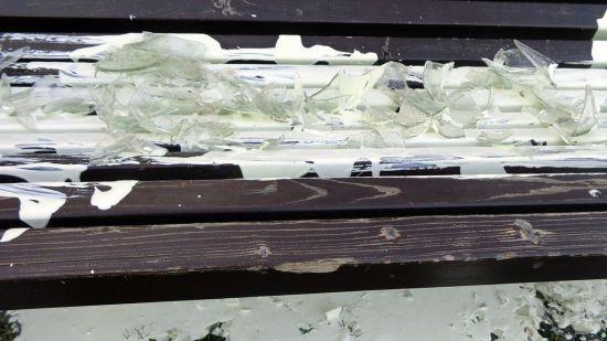 Eine Parkbank wurde mit Farbe beschmiert und mit Scherben belegt. Foto aus dem Bekennerschreiben.
