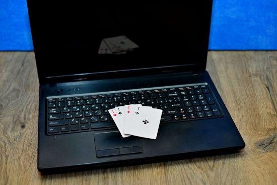 Vier Karten liegen auf der Tastatur eines Laptops.