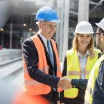 Executive shaking construction workers hand at construction site.