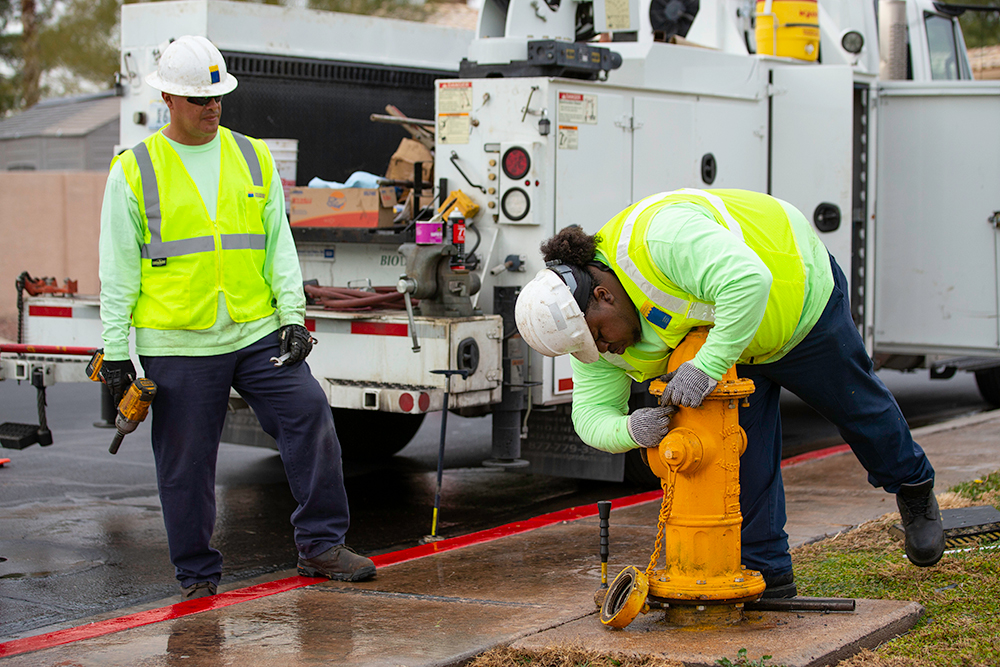 "Gabe Castillo (left) and Darius Whitfield help maintain more than 40,000 fire hydrants. ""We don't just repair fire hydrants. To me, we actually save lives,"" Whitfield says."