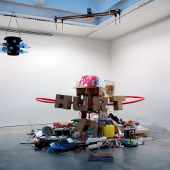 Planet Hurt // Electrical Motor, Transformer, Electrical Cable, Wood, Clamps, Plastic/Metal Piping & Wire, Cat Gut, TV, Cardboard Boxes, Buckets, Insulation, Electrical Fan, Polyurethane, Glue, Glitter, Foot Stool, Various kinds of Refuse, Spare Parts from Dismantled Sculptures // 350 x 470 x 400 cm // 2006