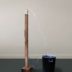 The Jimmy Durham Spilt Milk Fountain: Deluxe Version // Wood, Screen, Printed Text, Metal Brackets, Bin, Water Pump, Hosing, Water, Paint, Milk Carton // 250 x 200 x 90 cm // 2005