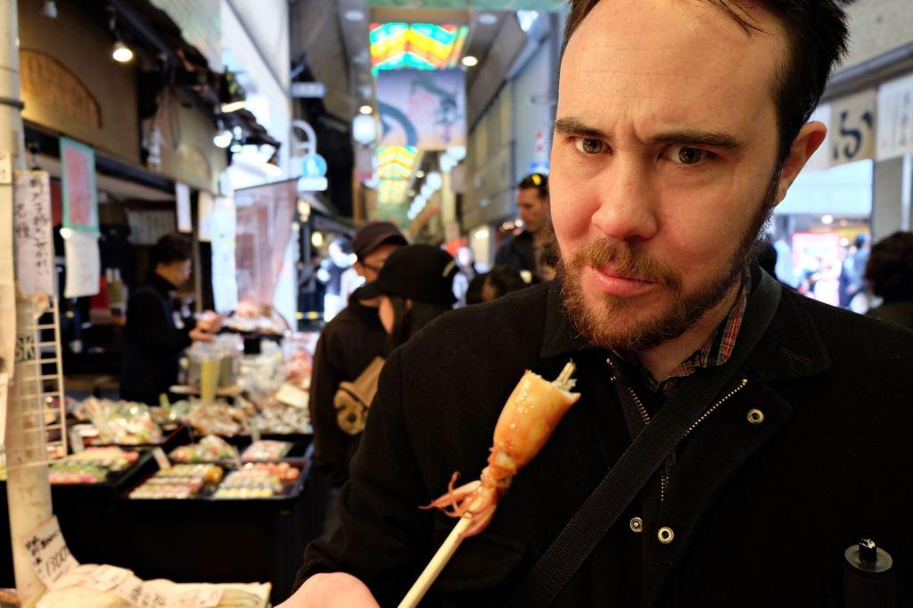 Kyoto Nishiki Market Dan eating squid on a stick