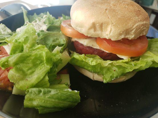 bilde av en burger i brød med salat på siden