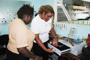 Chantel Charles (right) fixes a cabinet lock at Liamuiga Security Company under the watchful eye of her supervisor, Ms Rose Pemberton.