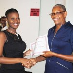 Minister of Health the Hon Marcella Liburd (right) presents a certificate to the programme's valedictorian Ms Selena Garnett.