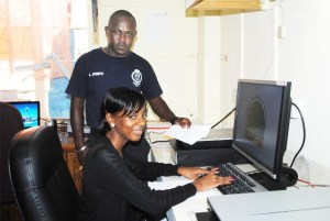 Ms Melissa Mason operating the Automated Fingerprints Identification System, under the watchful eye of Constable Joseph