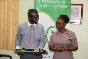 Head of the Information Technology Department in the Nevis Island Administration Quincy Prentice (L) with Director of the St. Christopher and Nevis Social Security Mrs. Sephlin Lawrence at the Ministry of Finance Conference room on May 22, 2014, during a handing over ceremony of survey equipment for the Ministry of Finance from the Social Security Board