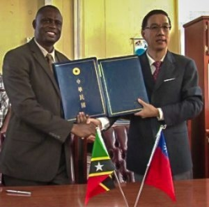 Ambassador Tsao (left) and Minister Carty after the signing of an Agricultural Technical Cooperation Agreement MOU, December 10, 2013