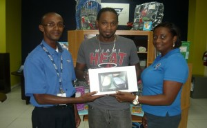 Mr. Ferguson receiving his prize from Mr. Alphonse Pennyfeather (Manager, TDC Business Centre along with  Ms. Jonelle Rawlins Drew, Client Relations and Marketing Manager