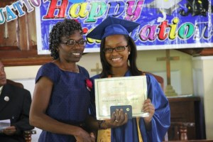 Valedictorian of the 2014 Graduating Class of the Gingerland Secondary School Cordiesere Walters receives her certificate from Patron, Jennifer Liburd, at the 41st Annual Graduation Ceremony of the Gingerland Secondary School at the Gingerland Methodist Church on November 27, 2014