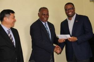 Premier of Nevis Hon. Vance Amory (l) hands over cheque from the Republic of China (Taiwan), for assistance to the Nevis Cultural Development Foundation, to Deputy Premier and Minister of Culture Hon. Mark Brantley on April 19, 2016, at Bath Hotel. Republic of China (Taiwan) Ambassador to St. Kitts and Nevis His Excellency George Gow Wei Chiou looks on