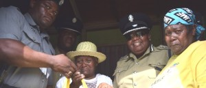 Ms Venus Virginia Mason accepting a gift basket from ACP Hughes and officers from the Sandy Point Police Station