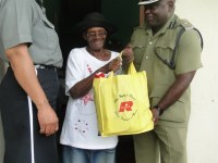 Supt Trevor Mills Head of Nevis Division presenting a gift basket to Ms Marion Herman of Newcastle Village