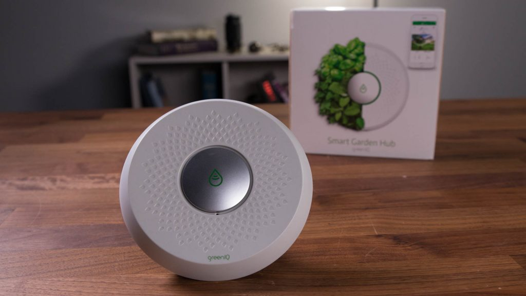 Smart Home, outdoor tech, smart irrigation controller, GreenIQ, the GreenIQ sits on top of a table, with its box in the backdrop.