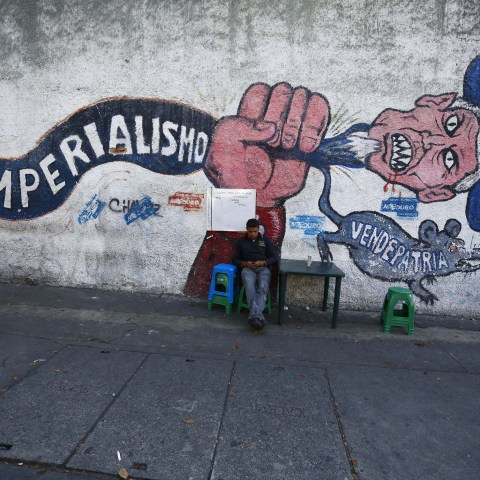 """9 March 2015: A man sits in front of graffiti, which reads """"imperialism"""" in Caracas, after the United States ordered sanctions against seven officials from the oil-rich country. (Photograph by Jorge Silva/Reuters)"""