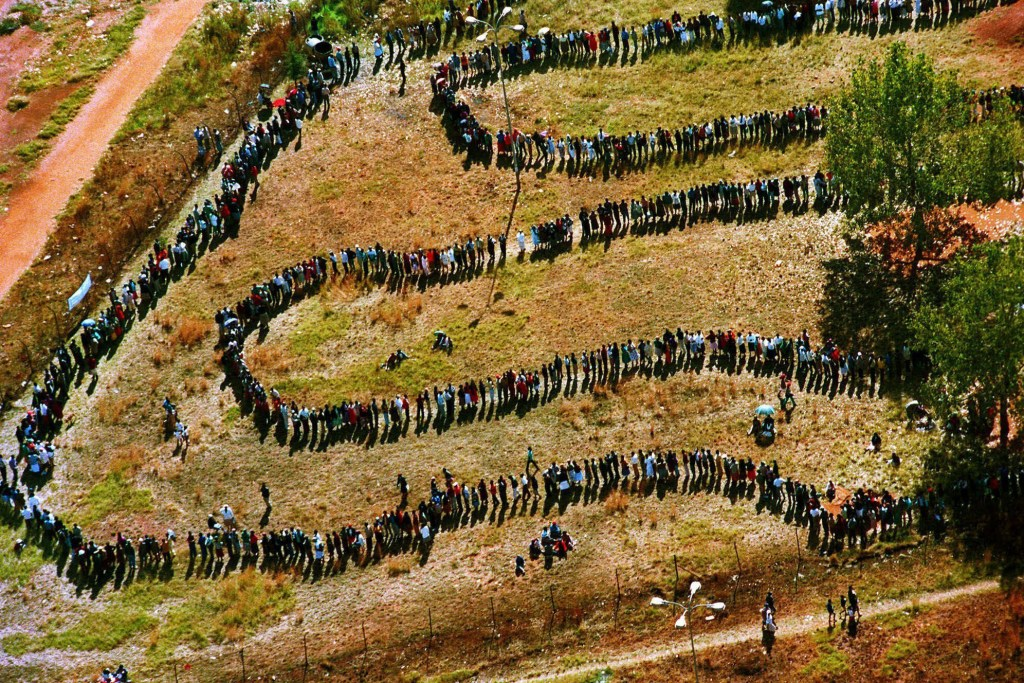 27 April 1994: People queuing at a primary school to cast their votes in Soweto as South Africa went to the polls for its first democratic elections. The seminal photo became known to insiders as The Helicopter Pic. (Photograph by AP Photo/Denis Farrell)