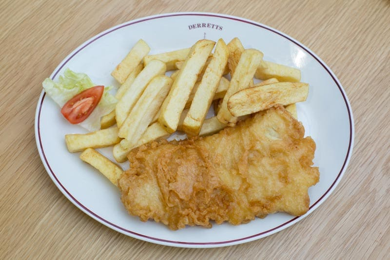 Golden crispy battered cod and chips in the restaurant